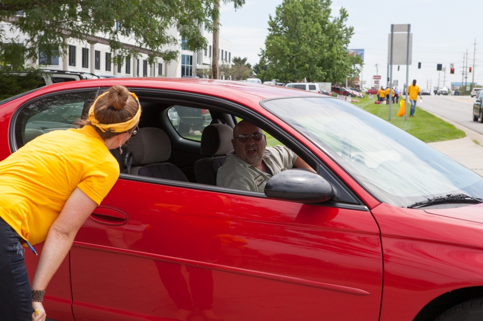 Organizer with United Food and Commercial Workers union engages a worker leaving the AdvancePierre plant in West Chester. Photo: Mike Brown, C4AD.