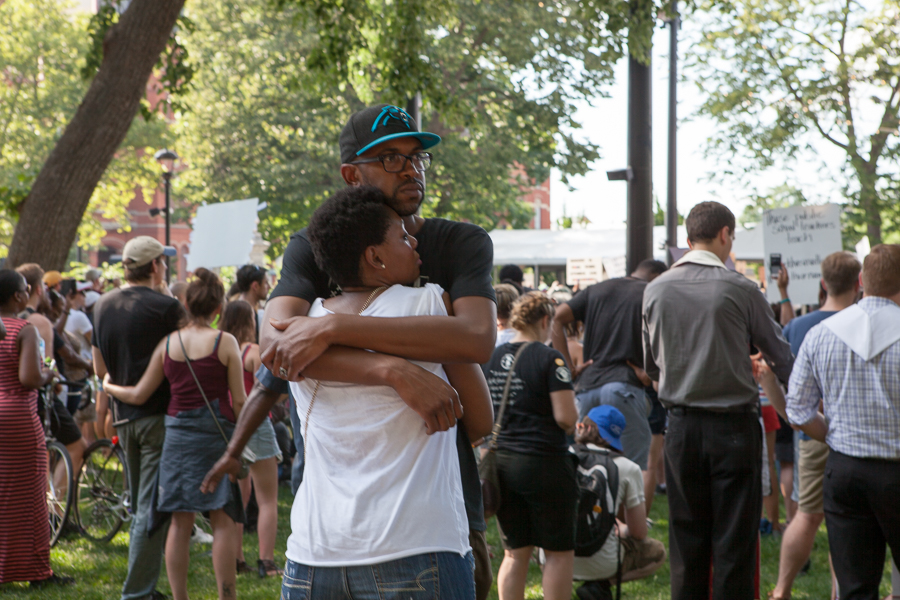 A couple comfort each other as the names of African-Americans killed during the last week by police are announced. Photo: Mike Brown, C4AD.