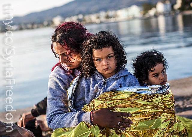 A Syrian family waits after being escorted into the harbor by the Greek Coast Guard, which found them drifing offshore on June 4, 2015, in Kos, Greece. Public domain by Freedom House, https://www.flickr.com/photos/syriafreedom/