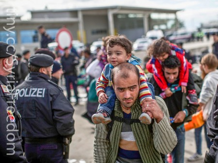 A Syrian migrant carries a child as he waits in line to board a bus organized by the Austrian government in Hegyeshalom, Hungary. Public domain by Freedom House, https://www.flickr.com/photos/syriafreedom/